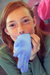 Picture of girl blowing up lab glove
