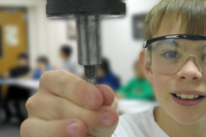 Boy with safety goggles looking at equipment